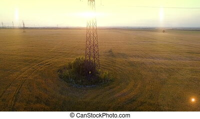 AERIAL High-voltage tower summer warm evening light camera...