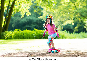 Child riding skateboard in summer park. Little girl learning...