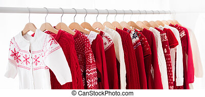 Clothes rack with red Christmas knit wear. Wardrobe with...