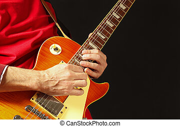 Hands of musician playing the electric guitar on dark...