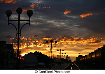 A train runs on the tracks at station i during a beautiful sunrise.
