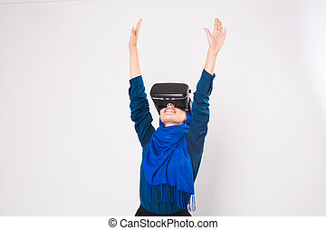 Asian muslim woman wearing hijab using VR headset glasses of...
