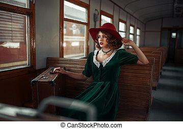 Beautiful woman in retro train, old wagon interior. Railroad...