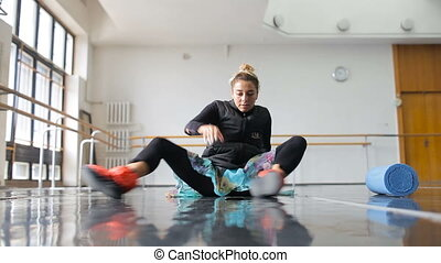 Ballerina does warm-up before training in a large ballet...