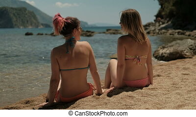 Two young women synchronously fall on their backs on beach....