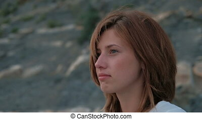 Close-up shot of woman face rests on beach on lake mountains...