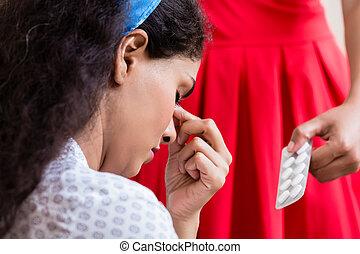 Woman giving medication against headache