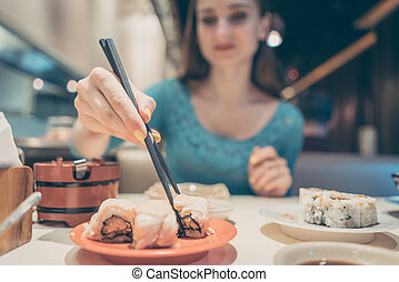 Woman eating sushi food in Japanese restaurant