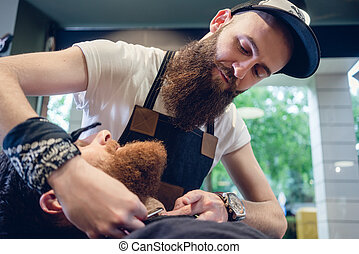 Bearded young man ready for shaving in the hair salon of a...