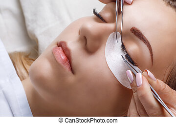 Eyelash Extension Procedure. Woman Eye with Long Eyelashes....