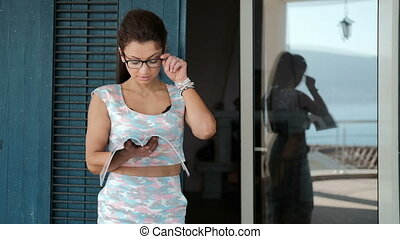 Woman in glasses on veranda carefully studying magazine....