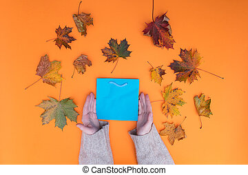 Above view at female hands holding shopping bag with autumn...