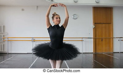 A professional ballerina in a black pack dances in a large...