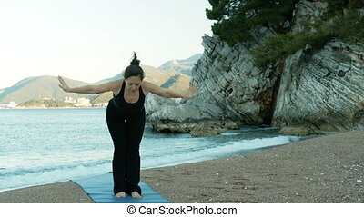 An adult woman performs yoga exercises on seashore at cliffs.