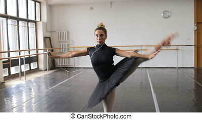 The ballerina practices in the big hall and listens to music on the smartphone