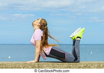 Woman doing yoga next to sea - Super fit attractive young...