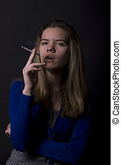 smoking girl - young female smoking addict over black