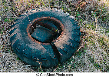 Old truck tire rubber lying on the grass.