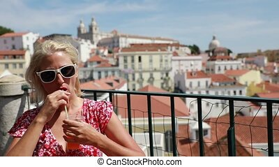Lisbon tourist viewpoint - Happy tourist woman drinking...