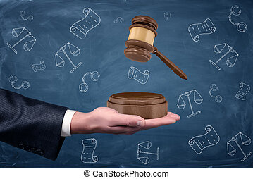 A businessman's hand holding a sound block palm up and a wooden gavel hovering above it.