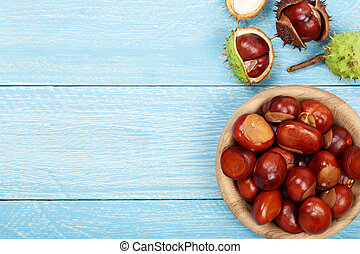 chestnut in bowl on blue wooden background with copy space...