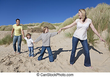 Mother, Father and Two Boys Holding Hands At Beach