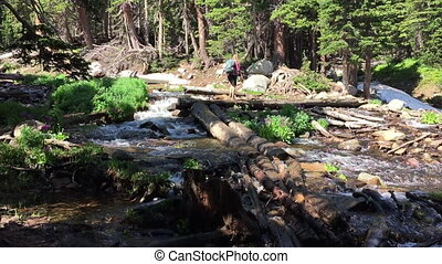 Hiker Crosses a stream near Mitchell Lake Colorado - Hiker...