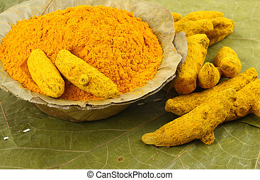 Pile of turmeric powder with barks of turmeric