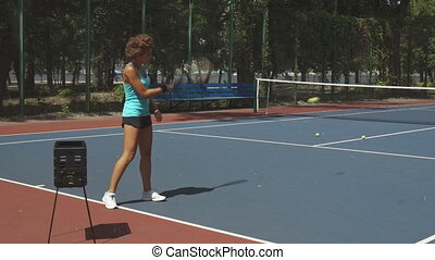 Curly woman hitting tennis balls - Girl is on a tennis...