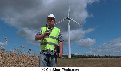 Electrician on the walkie-talkie near wind turbines