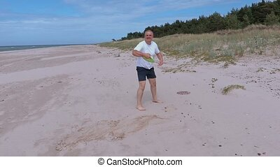 Man playing with Frisbee disc on the beach near sea
