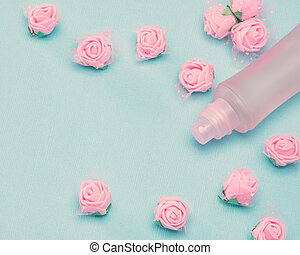 Perfume spray bottle and small pink roses on blue textured...