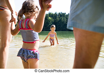 Little girls with lake. Sunny summer. - Little girls with...