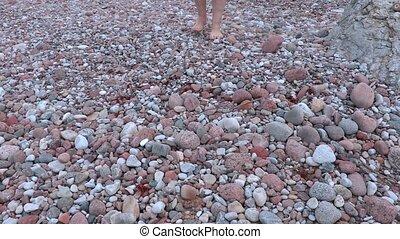 Man walking barefoot on stones