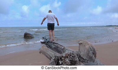 Man trying to hold the balance on the tree near sea