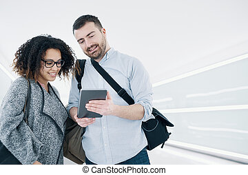 Couple ready to go on vacation using travel app on digital...