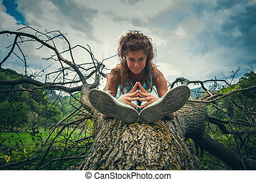 young woman practice yoga outdoor on huge fell tree on the...