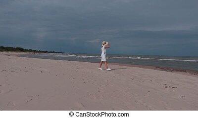 Woman in white dress walking near sea