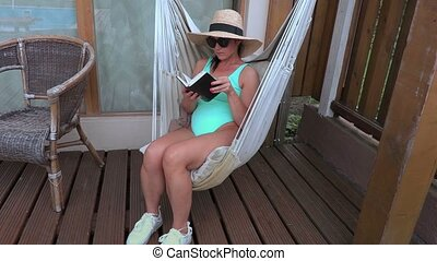 Woman with notebook relaxing in hammock
