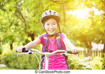 Happy girl  riding bicycle in the park