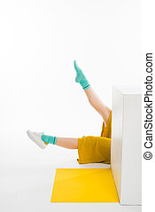 female legs behind white cube - female legs in yellow pants...