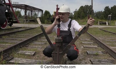 Railway employee speaks by phone at the switches
