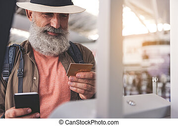 Cheerful pensioner looking at plastic money - Portrait of...