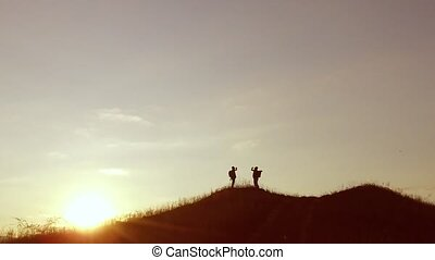 people group of tourists walking travel on top of a sunset silhouette mountain. slow video tourists people group go nature