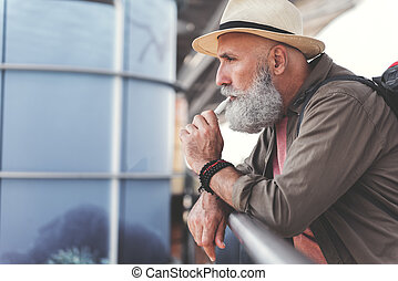 Mindful bearded elder man smoking