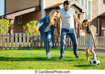 Happy family playing football in the yard