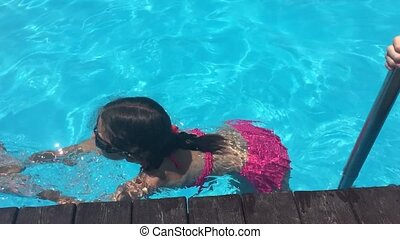 kids bathe in the pool. water children boy and girl swimming...