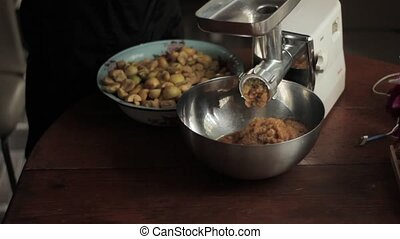 squeezing apple with apple press for applesauce in small...
