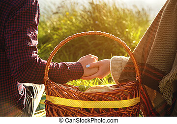 Close-up of a young couple holding hands over a fruit basket on a picnic