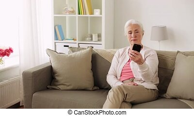 senior woman with smartphone taking selfie at home -...